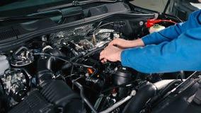 De tovenaar controleert draden onder de kap van een auto stock footage