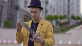 De tovenaar in gele jasje en hoed heeft pret met speelkaarten stock video