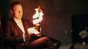 De tovenaar houdt een brandende beurs in zijn hand stock videobeelden