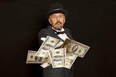De tovenaar toont met dollarsbankbiljet Geïsoleerd op Zwarte Royalty-vrije Stock Fotografie