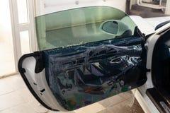 De tovenaar voor het installeren van extra materiaal plakt een tintfilm op het zij voorglas van de auto en bespuit water nat te w stock afbeeldingen