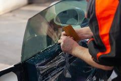 De tovenaar voor het installeren van extra materiaal plakt een tintfilm op het zij voorglas van de auto en vlakt het met de hand  royalty-vrije stock afbeeldingen