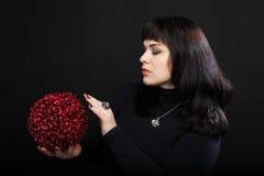 De tovenaarsvrouw houdt rode magische bal Royalty-vrije Stock Foto