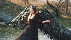 De tovenares in lange zwarte uitstekende kleding met kantkokers op weg, houdt haar grote en sterke vleugels met zachte handen, da stock video