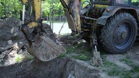 De tractor bevindt zich dichtbij grondkuil Backhoe stapelt omhoog het grondclose-up op stock video