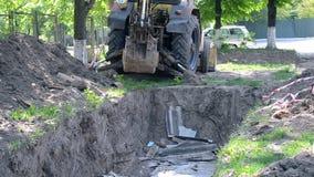 De tractor bevindt zich dichtbij grondkuil Backhoe stapelt omhoog het grondclose-up op stock footage
