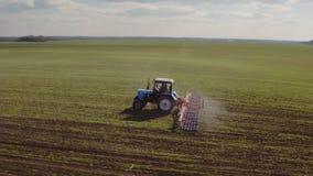 De tractor cultiveert het land op het gebied in de vroege lente De cameravliegen rond stock videobeelden