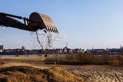 De tractor de emmer dumpt het zand op de bouwwerf royalty-vrije stock afbeeldingen