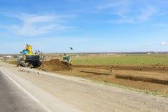 De tractor en het graafwerktuig kiezen grond van de duidelijke plaatsen voor archeologisch onderzoek van het district vóór bouw v royalty-vrije stock foto's