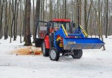 De tractor in het hout in de winter stock afbeeldingen