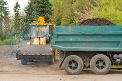 De tractor laadde de aarde in de vrachtwagen Ternopil De landwerken 04 27 2017 stock foto