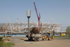 De tractor laadt droge takken in de vrachtwagen op de achtergrondbouw van een nieuwe Volgograd-Arena ` van het voetbalstadion ` v stock foto's
