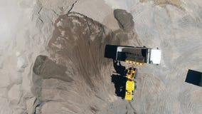 De tractor laadt een vrachtwagen met puin stock footage