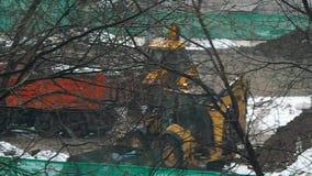 De tractor laadt van vrachtwagen op de bouwwerf in de winter stock footage