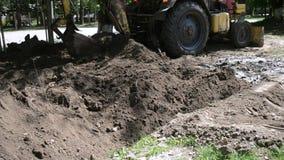 De tractor maakt kuiltjes in de grond stock videobeelden