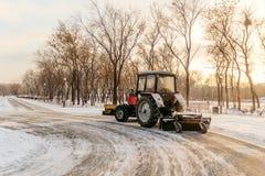 De tractor maakt sneeuw in het park schoon, die materiaal schoonmaken Royalty-vrije Stock Fotografie