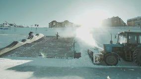 De tractor maakt sneeuw schoon Een snowboarder voert een truc uit stock video