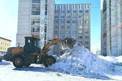 De tractor maakt sneeuw in de yard schoon en verzamelt een stapel stock fotografie