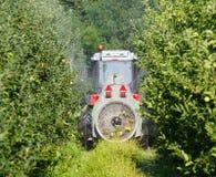 De tractor met een landbouwspuitbusmachine met grote ventilator, spreidt pesticiden in een appelboomgaard uit stock foto's