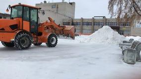 De tractor met emmer maakt of verwijdert sneeuw in één hoop schoon Sneeuwverwijdering in het stadsvierkant stock footage