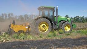 De tractor met ploeg cultiveert grond in gebied en partij van stofclose-up tegen blauwe hemel stock video