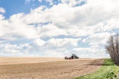 De tractor perst de grond na het planten met rollen samen Stock Foto's