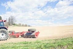 De tractor perst de grond na het planten met rollen samen Stock Afbeelding