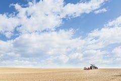 De tractor perst de grond na het planten met rollen samen Stock Fotografie
