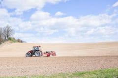 De tractor perst de grond na het planten met rollen samen Royalty-vrije Stock Fotografie