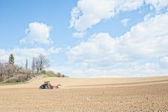 De tractor perst de grond na het planten met rollen samen Stock Foto