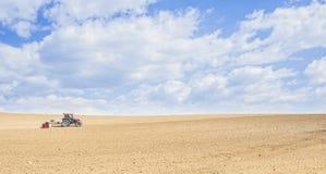 De tractor perst de grond na het planten met rollen samen Royalty-vrije Stock Afbeeldingen