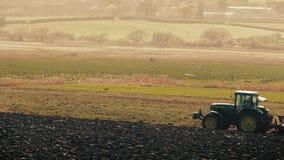 De tractor ploegt Gebied met Vogels die rond zwermen stock footage