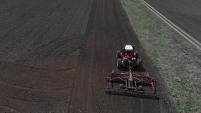 De tractor ploegt de grond op het gebied aan het begin van het het planten seizoen Een landbouwer bevindt zich op de sporen van v stock videobeelden