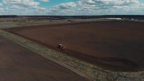 De tractor ploegt de grond op het gebied aan het begin van het het planten seizoen Luchtmening 4K stock videobeelden