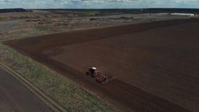 De tractor ploegt de grond op het gebied aan het begin van het het planten seizoen Luchtmening 4K stock video