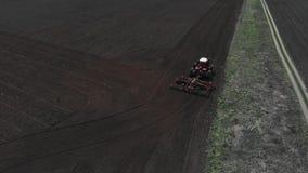 De tractor ploegt de grond op het gebied aan het begin van het het planten seizoen Tractortribunes op het gebied en stock videobeelden