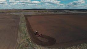 De tractor ploegt de grond op het gebied aan het begin van het het planten seizoen De tractor zet het gebied aan en stock footage