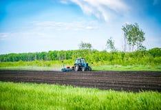 De tractor ploegt het land op het gebied in de lente Royalty-vrije Stock Foto's