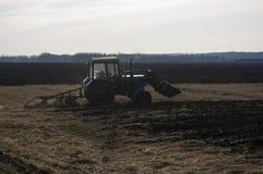 De tractor ploegt op de aarde in de lente Stock Afbeeldingen