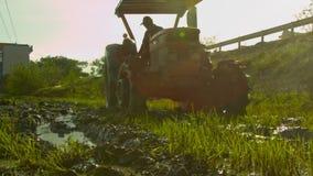 De tractor ploegt Padieveldbewegingen achteruit Voorwaarts door Wegclose-up stock footage