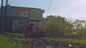 De tractor ploegt Padieveldkant van Dorpshuis langs Weg stock video
