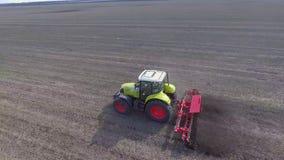 De tractor reist snel over het gebied, cultiveert de aarde zodat de vochtigheid geen verloren Luchtfotografie krijgt stock video