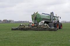 De tractor spuit vloeibare mest op een gebied in Stock Afbeeldingen