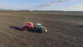 De tractor trekt een grote zaaimachine over het gebied Het zaaien campagne in de vroege lente, landelijk landschap Zachte nadruk  stock footage