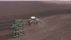 De tractor trekt een landbouwapparaat voor harrowing het land Het de lentewerk op het gebied, luchtfotografie stock videobeelden