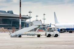 De tractor trekt de passagier het inschepen treden bij de luchthavenschort naast aan de terminal stock afbeelding