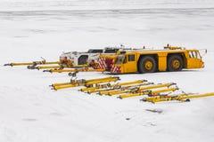 De tractor van het vliegtuigslepen bij het parkeren bij de schort van de luchthavenwinter Stock Foto