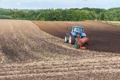 De Tractor van landbouwersplowing field with Stock Fotografie