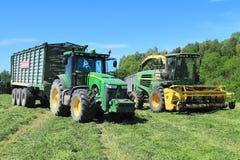 De tractor van wieljohn deere 8335R met de aanhangwagen en het veevoeder die John Deere 7450 oogsten combineren Royalty-vrije Stock Afbeeldingen