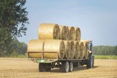 De tractor verwijdert balen van hooi uit het gebied na oogst het Schoonmaken korrelconcepten Voltooiing van het landbouwbedrijf royalty-vrije stock afbeeldingen
